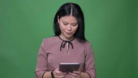 Lanzamiento del primer de la hembra asiática atractiva joven con el pelo negro usando la tableta con el fondo aislado en verde almacen de metraje de vídeo