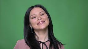 Lanzamiento del primer de la hembra asiática atractiva joven que sonríe feliz delante de la cámara con el fondo aislado en verde almacen de metraje de vídeo