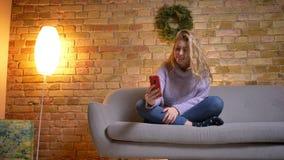 Lanzamiento del primer de la hembra atractiva caucásica adulta que tiene una llamada video en el teléfono mientras que se sienta  almacen de video