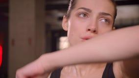Lanzamiento del primer de la hembra atractiva joven del atleta que se resuelve y que suda en el gimnasio dentro almacen de metraje de vídeo