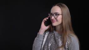 Lanzamiento del primer de la hembra atractiva joven del inconformista en los vidrios que tienen una conversación sobre el teléfon almacen de video
