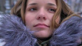 Lanzamiento del primer de la hembra caucásica atractiva joven con el pelo moreno en un abrigo de invierno en un día frío nevoso a metrajes