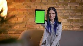 Lanzamiento del primer de la hembra caucásica bonita joven con el pelo teñido usando la tableta y mostrar una pantalla verde a la almacen de metraje de vídeo