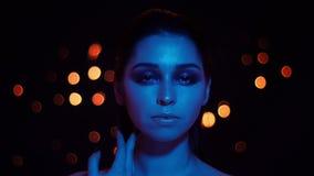 Lanzamiento del primer de la hembra caucásica bonita joven con maquillaje imponente con las luces azules de la luz de neón y del  almacen de video
