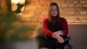 Lanzamiento del primer de la hembra caucásica bonita joven que mira una película en la TV que es tocada y el griterío metrajes