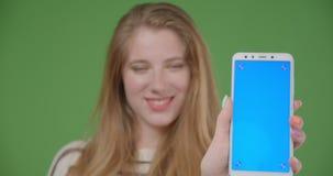 Lanzamiento del primer de la hembra caucásica bonita joven usando el teléfono y mostrar la pantalla azul a la cámara que sonríe f metrajes
