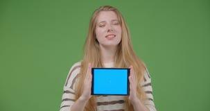 Lanzamiento del primer de la hembra caucásica bonita joven usando la tableta y mostrar la pantalla azul a la cámara que sonríe fe almacen de metraje de vídeo