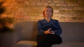 Lanzamiento del primer de la hembra caucásica del eldery que ve una TV el sirtting en el sofá en un apartamento acogedor dentro almacen de video