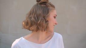 Lanzamiento del primer de la hembra caucásica linda joven con los bollos del pelo que sonríe feliz dando vuelta a la cámara con l almacen de metraje de vídeo