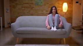 Lanzamiento del primer de la hembra caucásica morena bonita joven que es sentada deprimida y agujereada triste en el sofá en un a metrajes