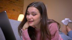 Lanzamiento del primer de la hembra caucásica morena bonita joven que mira un vídeo divertido en el ordenador portátil y que es d almacen de metraje de vídeo