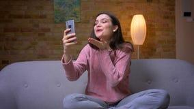 Lanzamiento del primer de la hembra caucásica morena bonita joven que tiene una llamada video en el teléfono y sentada sonriente  metrajes