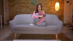 Lanzamiento del primer de la hembra caucásica morena bonita joven que ve la TV con el entusiasmo y la curiosidad que se sientan e almacen de video