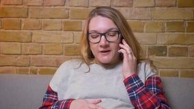 Lanzamiento del primer de la hembra embarazada joven que habla en el teléfono mientras que se sienta en el sofá en un apartamen almacen de video
