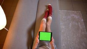 Lanzamiento del primer de la hembra joven usando la tableta con la pantalla verde de la croma con el anuncio en él Las piernas d almacen de video
