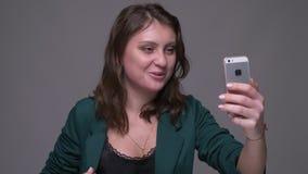 Lanzamiento del primer de la hembra morena atractiva adulta que tiene una llamada video en él llama por teléfono a hablar emocion almacen de video