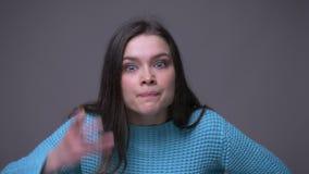 Lanzamiento del primer de la hembra morena bonita joven que es en cámara de mirada enojada y furiosa con el fondo aislado en gris metrajes
