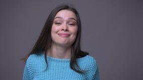Lanzamiento del primer de la hembra morena bonita joven que hace las expresiones faciales divertidas que miran la cámara con el f almacen de video