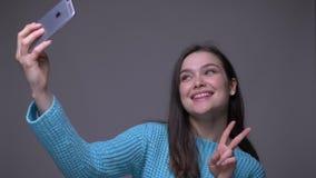 Lanzamiento del primer de la hembra morena bonita joven que toma selfies en el teléfono y que sonríe alegre con el fondo almacen de metraje de vídeo