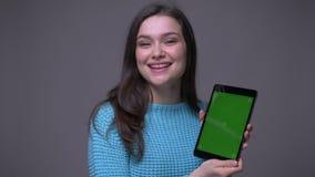 Lanzamiento del primer de la hembra morena bonita joven usando la tableta y mostrar la pantalla verde de la croma que mira la cám almacen de video