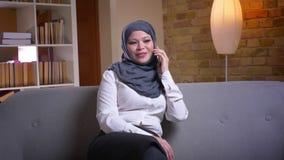 Lanzamiento del primer de la hembra musulmán adulta en el hijab que tiene una conversación el teléfono mientras que se sienta en  almacen de metraje de vídeo
