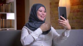 Lanzamiento del primer de la hembra musulmán adulta en el hijab que tiene una llamada video en la tableta mientras que se sienta  almacen de metraje de vídeo