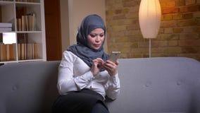 Lanzamiento del primer de la hembra musulmán adulta en hijab usando el teléfono mientras que se sienta en el sofá dentro almacen de metraje de vídeo