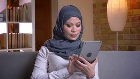 Lanzamiento del primer de la hembra musulmán adulta en hijab usando la tableta mientras que se sienta en el sofá dentro en casa almacen de video