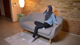Lanzamiento del primer de la hembra musulmán atractiva joven en hijab que invita al teléfono mientras que se sienta en el sofá de almacen de metraje de vídeo