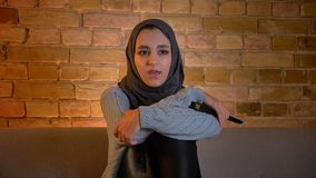 Lanzamiento del primer de la hembra musulmán atractiva joven en hijab que ve la TV con el entusiasmo y que lleva a cabo rato tele metrajes