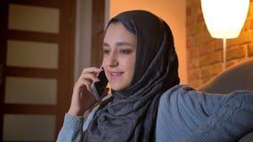 Lanzamiento del primer de la hembra musulmán atractiva joven que invita al teléfono y que habla emocionalmente mientras que se si almacen de metraje de vídeo