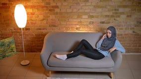 Lanzamiento del primer de la hembra musulmán atractiva joven que tiene una reclinación de la llamada de teléfono tranquila en el  metrajes