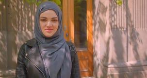 Lanzamiento del primer de la hembra musulmán bonita joven en hijab que sonríe alegre mirando la cámara en la calle en el urbano metrajes