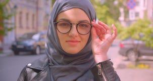 Lanzamiento del primer de la hembra musulmán bonita joven en hijab y de vidrios que sonríen feliz mirando la cámara en la calle e metrajes