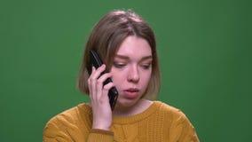 Lanzamiento del primer de la hembra de pelo corto atractiva joven que tiene una llamada de tel?fono que mira la c?mara con el fon almacen de metraje de vídeo