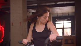 Lanzamiento del primer de la hembra de pelo largo del atleta atractivo joven que se resuelve en el orbitrek en el gimnasio dentro metrajes