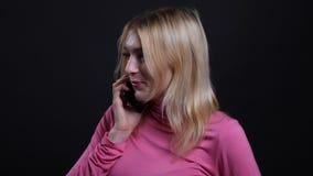 Lanzamiento del primer de la hembra rubia bonita joven que tiene una llamada de teléfono y que habla alegre con el fondo aislado  almacen de video