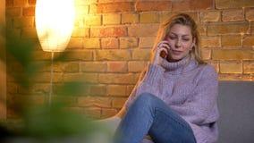 Lanzamiento del primer de la hembra rubia caucásica adulta que habla en el teléfono mientras que se sienta en el sofá dentro en e almacen de video