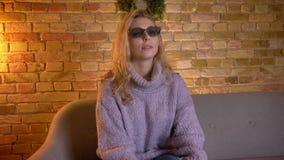 Lanzamiento del primer de la hembra rubia caucásica adulta que mira una película 3D en la TV mientras que se sienta en el sofá de almacen de video