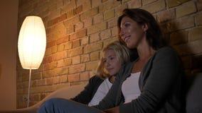 Lanzamiento del primer de la madre caucásica joven y su de la hija que miran la TV junta y la sonrisa Mamá que abraza a su muchac almacen de metraje de vídeo