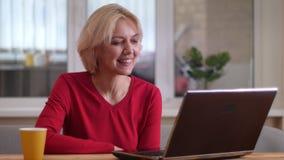 Lanzamiento del primer de la mujer caucásica envejecida que tiene una llamada video en el ordenador portátil que sonríe feliz den almacen de video