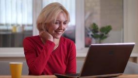 Lanzamiento del primer de la mujer caucásica envejecida que tiene una llamada video en el ordenador portátil que sonríe y que hab almacen de video