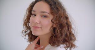 Lanzamiento del primer de la sonrisa femenina del caucásico rizado de pelo largo bonito joven alegre presentando delante de la cá almacen de video