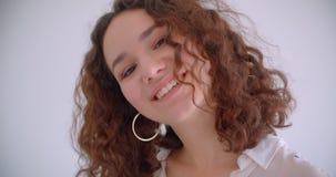 Lanzamiento del primer de la sonrisa femenina del caucásico rizado de pelo largo bonito joven feliz dando vuelta y presentando de almacen de video