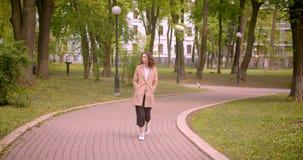Lanzamiento del primer de la sonrisa femenina del caucásico rizado de pelo largo joven feliz caminando hacia cámara al aire libre almacen de metraje de vídeo