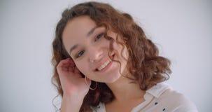 Lanzamiento del primer de la sonrisa femenina del caucásico rizado de pelo largo lindo joven alegre presentando delante de la cám almacen de video