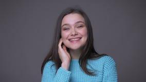 Lanzamiento del primer de la sonrisa femenina morena bonita joven en cámara alegre de mirada con el fondo aislado en gris almacen de video