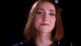 Lanzamiento del primer de la sonrisa femenina de pelo corto bonita joven en cámara alegre de mirada con las luces del bokeh en metrajes