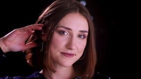 Lanzamiento del primer de la sonrisa femenina de pelo corto bonita joven en cámara feliz de mirada con las luces del bokeh en el  almacen de video