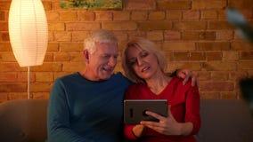 Lanzamiento del primer de la web mayor de la ojeada de los pares en la tableta que sonríe feliz sentándose en el sofá dentro en u metrajes